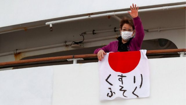 """Woman waving a flag reading """"shortage of medicine"""" from the ship"""