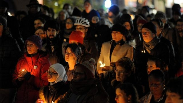 Community members hold candles at a vigil for the victims of the Pittsburgh Synagogue shooting at Cambridge City Hall in Cambridge, Massachusetts