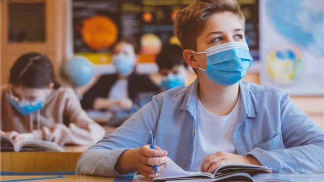 Menino de máscara em sala de aula
