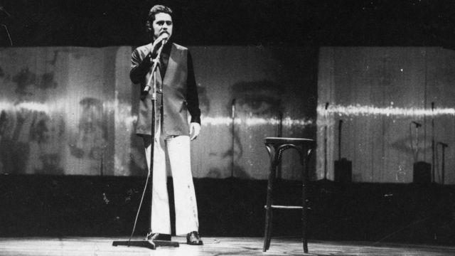 Chico Buarque no palco, em pé segurando em frente a microfone, em foto preto e branca