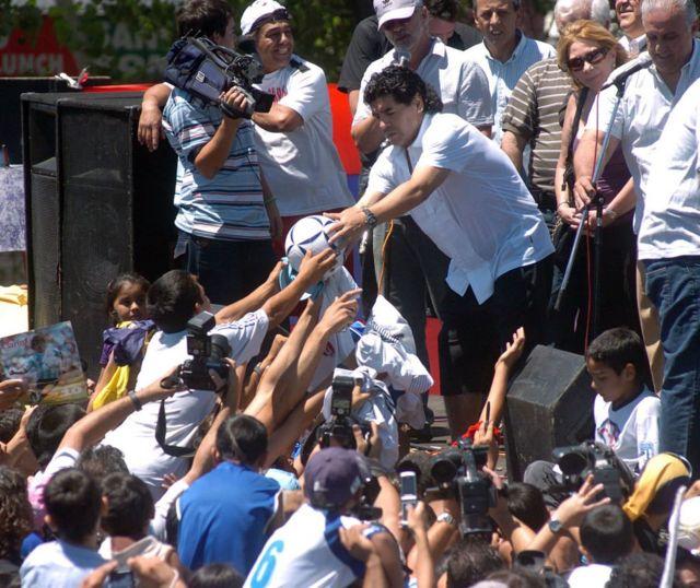 Maradona, 2008 yılında doğup büyüdüğü Villa Fiorito'da çocuklara futbol topu imzaladı.
