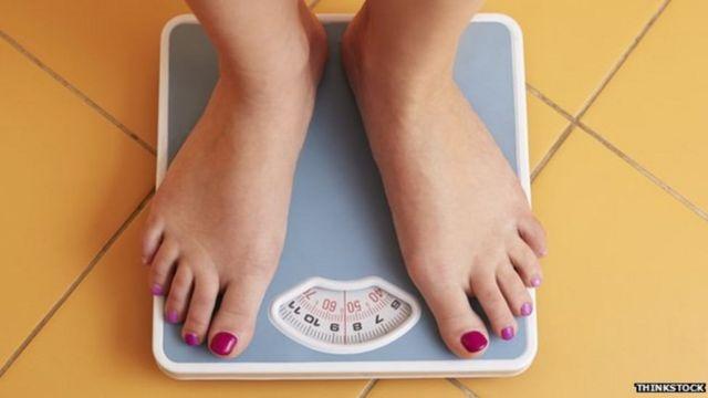 Mulher se pesa em balança