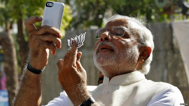 Indian leader Narendra Modi takes a selfie with his phone in Ahmedabad city on 30 April, 2014