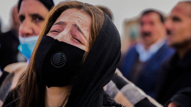Woman reacts during the mass funeral in Kocho on 6 February 2021