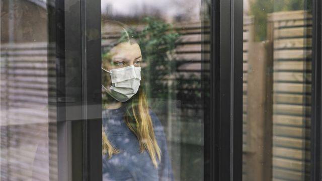 Una mujer con mascarilla mirando por la ventana.