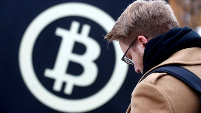 Un hombre delante de un afiche del bitcoin