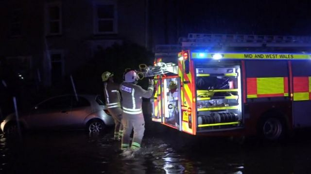 Firefighters in flood water