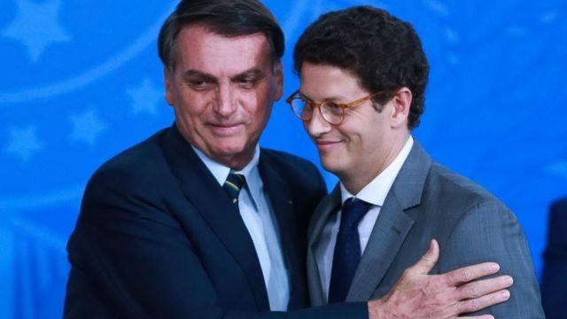 O presidente Jair Bolsonaro sorri e abraça o ministro do Meio Ambiente Ricardo Salles