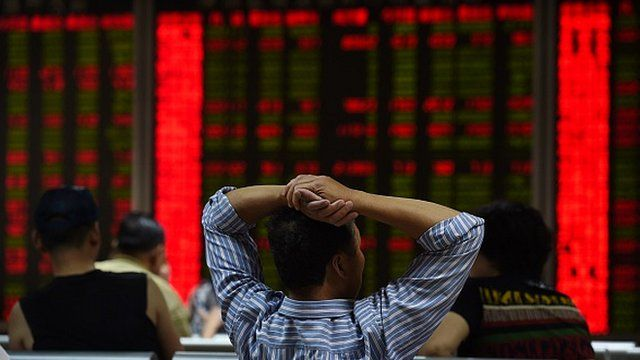 An investor looks at screens showing stock market movements in Beijing on 9 July 2015