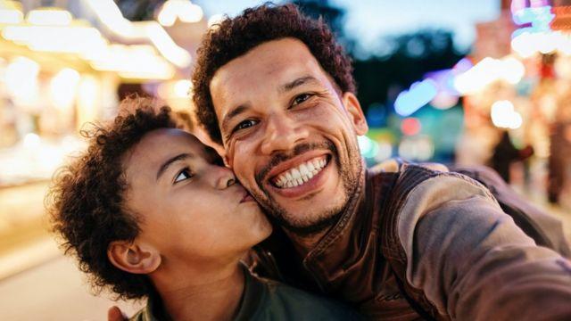 Un garçon embrasse la joue de son père alors qu'ils posent pour un selfie.