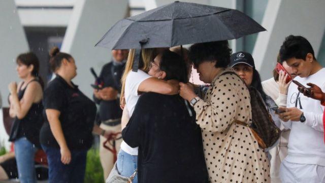Personas se abrazan fuera del edificio derrumbado en Miami.