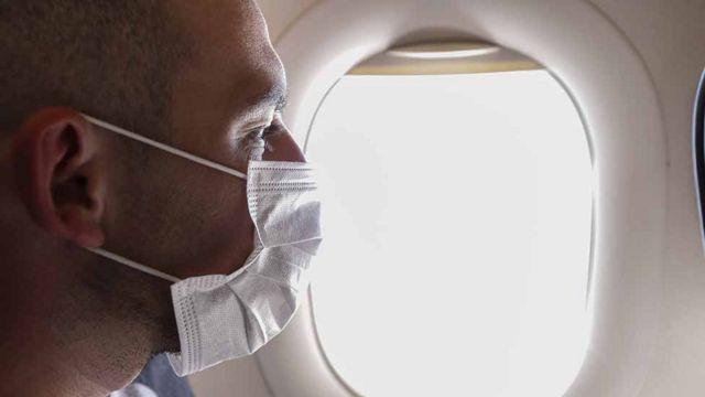 Hombre con mascarilla junto a la ventanilla del avión