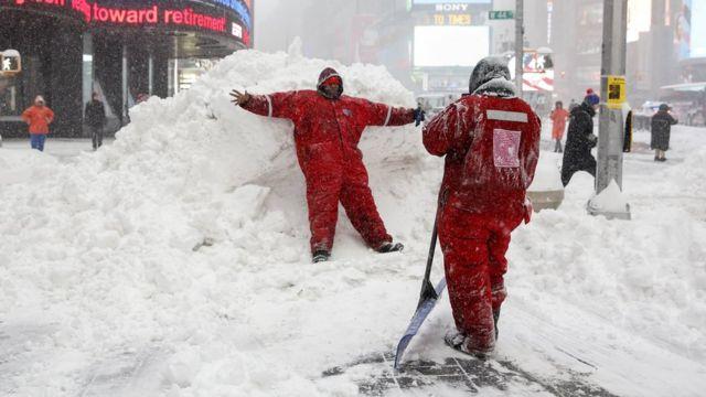 タイムズスクェアで除雪作業をしながら記念撮影する人たち(23日)