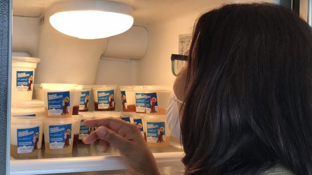 A woman in front of containers of yogurt in a refrigerator.