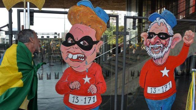 Dos dibujos de Dilma y Lula vestidos de presidiarios
