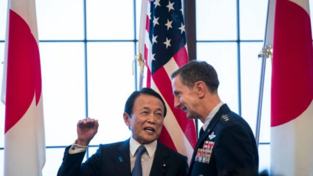 Japan's deputy prime minister Taro Aso (L) chats with Commander of the US Forces in Japan (USFJ), Lieutenant General Kevin Schneider (R) during the 60th anniversary commemorative reception of the signing of the Japan-US security treaty at Iikura Guesthouse in Tokyo on January 19, 2020.