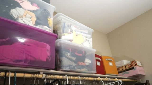 Shot of a closet, with clothes hanging on the rail and boxes piled up high on the shelves