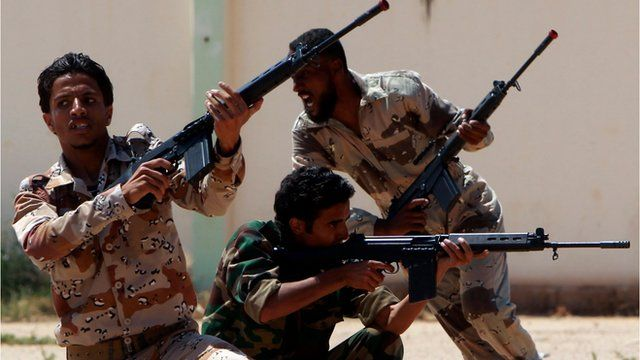Libyan rebel forces carry guns as they train in the rebel stronghold of Benghazi.