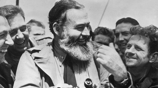 Militares ao lado de Ernest Hemingway, que trabalhou como correspondente de guerra