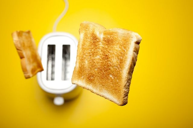 Dos rebanadas de tostada saltando del tostador.