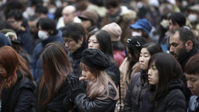 東京の追悼式典で黙祷する人たち(11日)