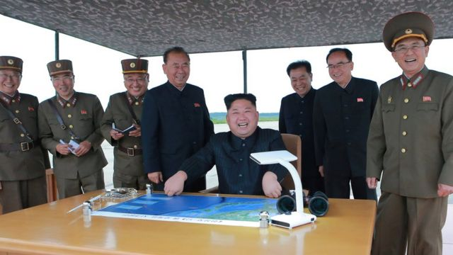 Kim Jong-un, seated in centre at a desk with a map, is seen surrounded by smiling officials and military personnel in an official photo