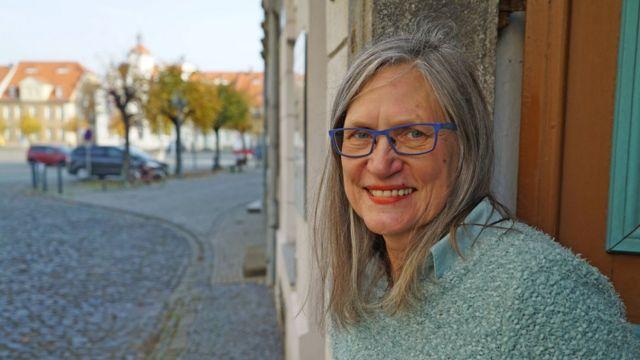 Eva Hauptfleisch sorri para foto de porta que dá para rua
