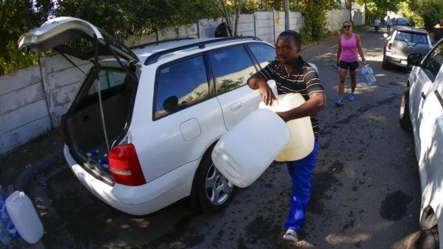 Un hombre lleva botellas de plástico para recoger agua en un manantial de Ciudad del Cabo.