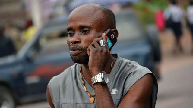 Un homme à Kinshasa tenant un téléphone