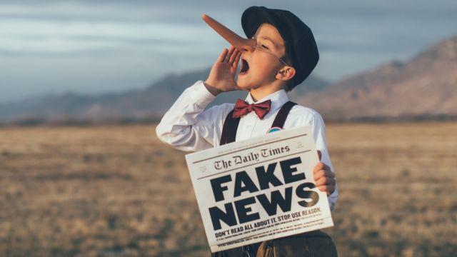 Niño con nariz de Pinocho y sosteniendo una periódico con Fake News.