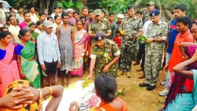 सामनाथ बघेल के शव के पास ग्रामीण और पुलिस अधिकारी
