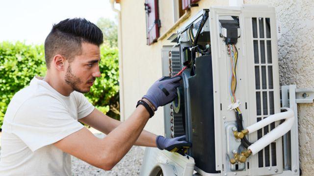 Hombre haciendo el mantenimiento de una unidad de aire acondicionado