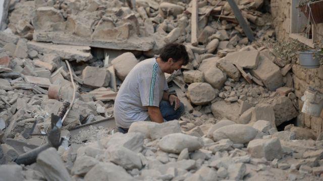 Un hombre se lamenta luego del terremoto que dejó en escombros a muchas casas.