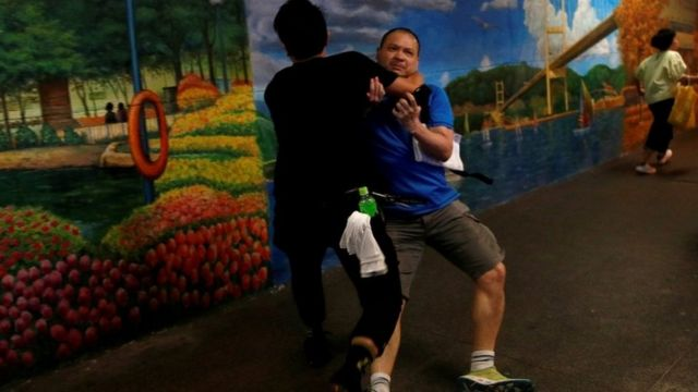A pro-government supporter is attacked by an anti-extradition supporter outside the office of Junius Ho in July