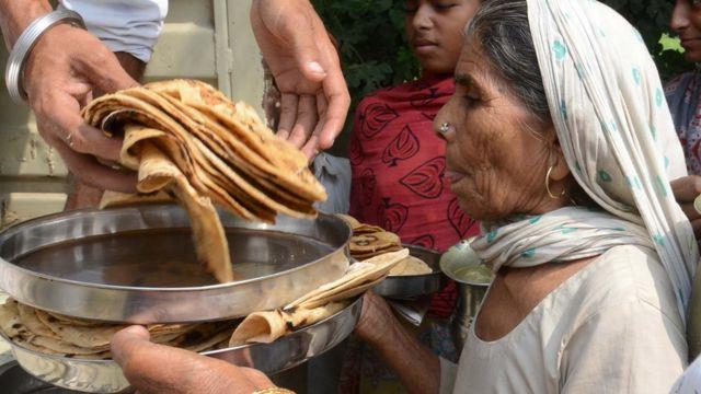 रोटी ले रही महिला