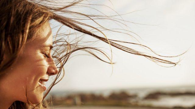 Una mujer sonríe con los ojos cerrados.