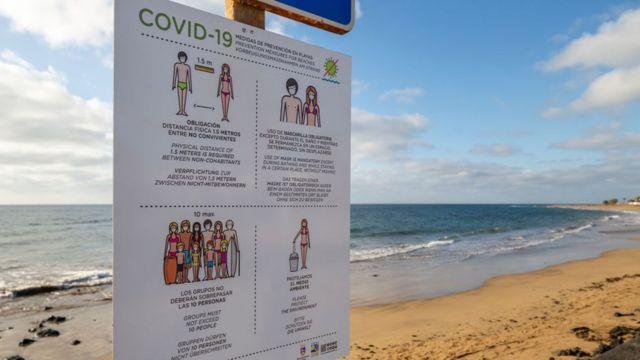 Playa desolada en Lanzarote, España, con un cartel sobre las restricciones del covid