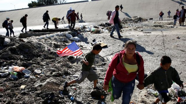 Migrants, part of a caravan of thousands travelling from Central America en route to the United States, run to cross Tijuana river near the border wall between the U.S. and Mexico in Tijuana