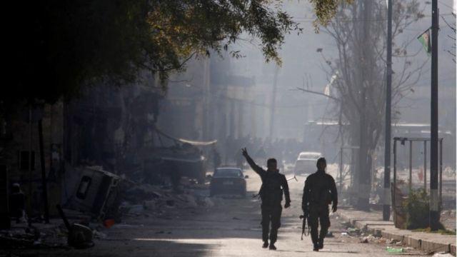 جنود من قوات الأسد يمشون في حلب.