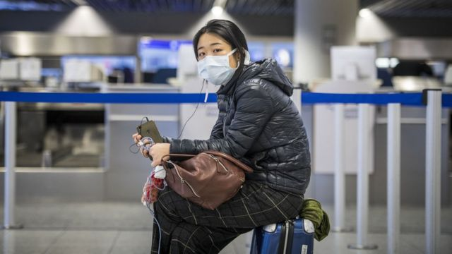 A Chinese girl at Frankfurt Airport, Germany, sitting on the suitcase and waiting at the check-in counter (12/3/2021)
