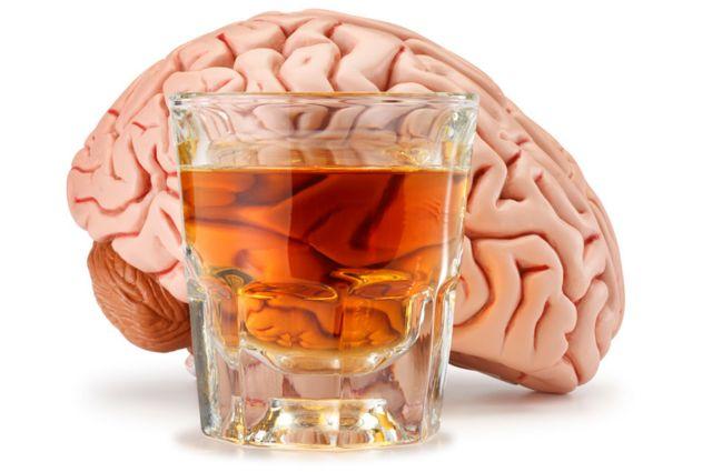 Un cerebro con un vaso de alcohol adelante.
