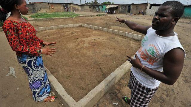 Noura Dosso (G) et Youssouf, se tiennent près d'une fosse commune où ont été enterrés les corps d'une trentaine de personnes qui auraient été tuées le 12 avril 2011 par des miliciens pro-Gbagbo, dans le quartier populaire de Yopougon à Abidjan, le 5 décembre 2011