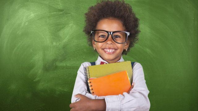 Menina de óculos segurando livros