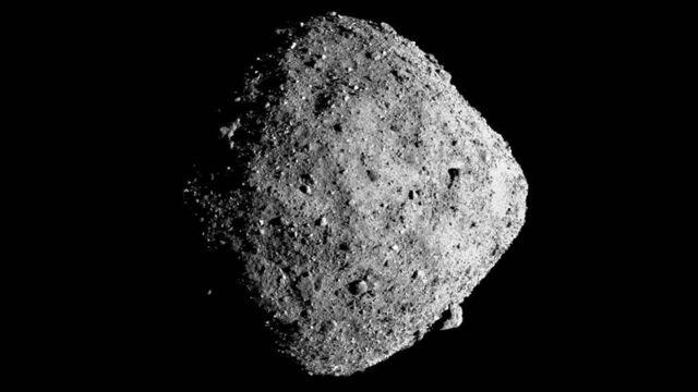 Imagem do Bennu no meio do espaço, com aparência de rocha e cor cinza