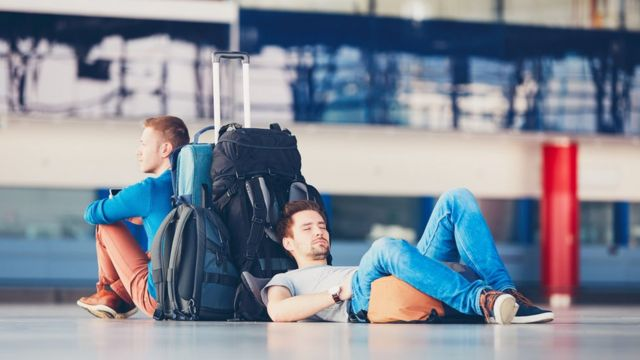Pasajeros esperando en aeropuerto.