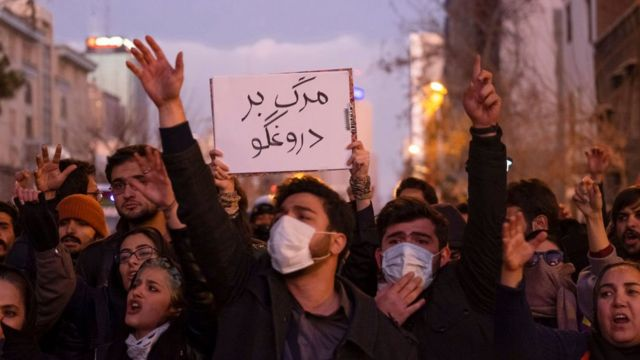 Iranians shout slogans as one of them holds-up a placard with a Persian script that reads, Death To The Liar, during a gathering to mark the victims of the crash