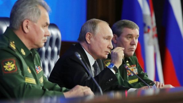 Russian President Vladimir Putin (C) and Russian Defence Minister Sergei Shoigu (L) take part in the annual meeting of the Defence Ministry board,