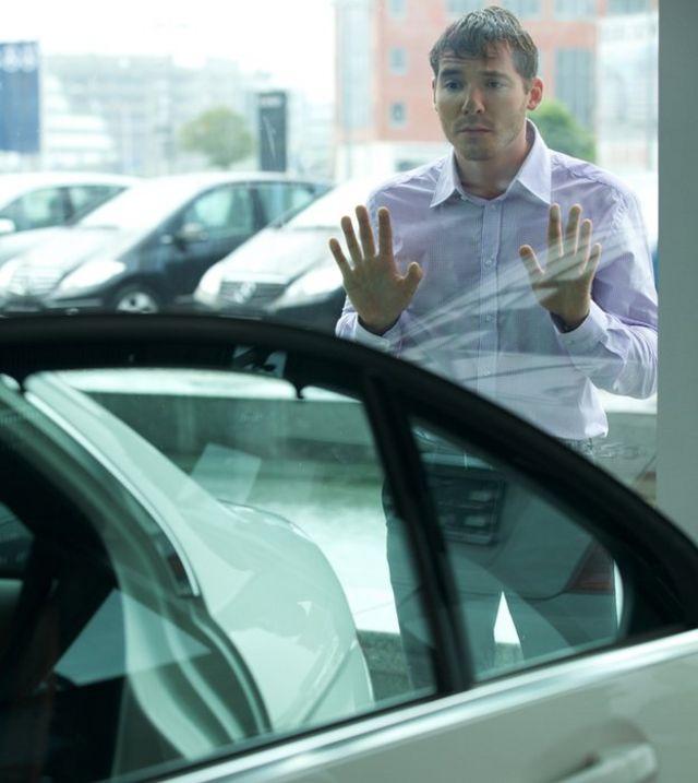 Hombre mirando por la ventana de un concesionario