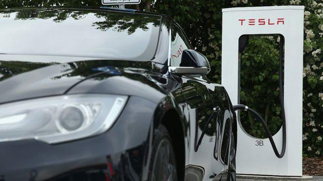 Un auto de Tesla junto a una estación de recarga.