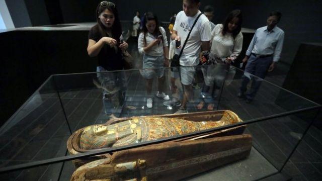 Visitantes olham para múmia no Louvre, em Paris
